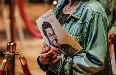 Fan holds the obituary of Chuck Berry as they pay their respects to the late rock 'n' roll visionary at The Pageant club in St. Louis