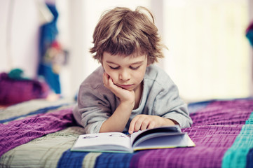 Cute little boy lying on bed reading book