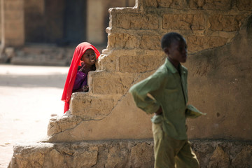 A girl looks from behind a wall in the town of Paoua