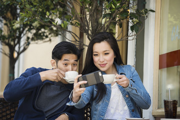 Smiling Chinese couple posing for cell phone selfie at outdoor cafe