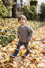 Mixed Race boy walking in autumn leaves