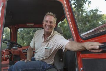 Smiling Caucasian man holding door of tractor