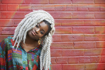 Pensive Black woman leaning on brick wall