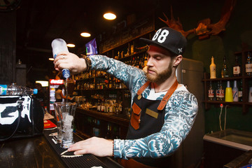 Steep bartender pours vodka in the bar