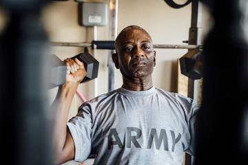 Black man lifting weights in garage