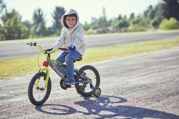 Hispanic boy posing on bicycle with training wheels