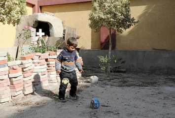 A child from a family who fled their home in Arish plays next to a cross outside a rented apartment on the edge of Suez Canal in Ismailia