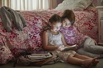 Caucasian sisters using digital tablet in bedroom
