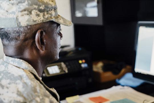 Black soldier using computer