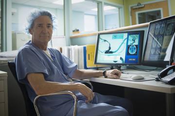Older Caucasian radiologist reading x-rays on computer