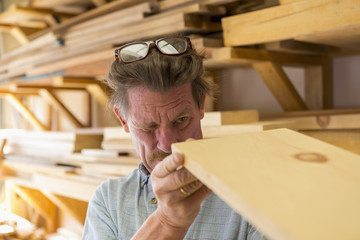 Caucasian carpenter eyeballing wooden plank in workshop