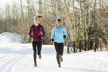 Women running together on snow covered road in winter