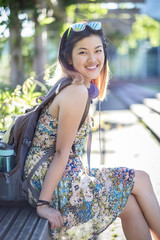 Portrait of smiling Chinese woman on bench wearing backpack