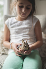 Girl looking at bunny while sitting on sofa