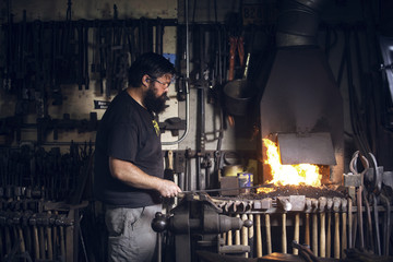 Side view of blacksmith working in workshop