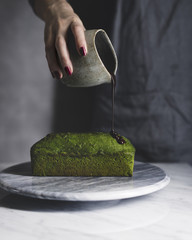 Midsection of woman pouring chocolate sauce on matcha pound cake
