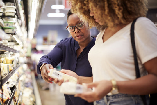 Black women examining cheese in grocery store