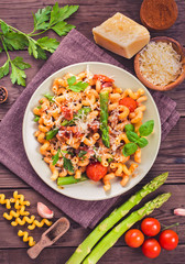 Italian cavatappi pasta with asparagus and tomatoes on wooden table, top view, toned