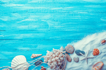 Sea sand and shells on turquoise background with copy space