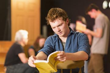 Caucasian teenage boy reading script in theater class