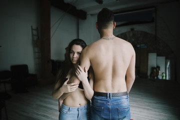 Caucasian woman hugging arm of man with bare back