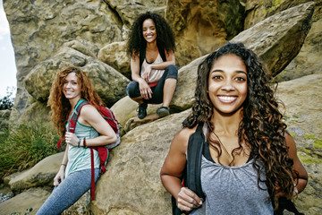 Smiling women carrying backpacks near rock formation