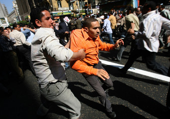 Egyptian plainclothes policeman arrests a protester during clashes in Cairo