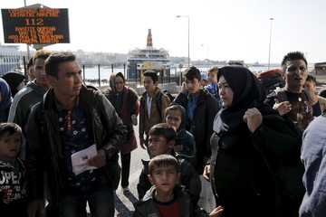 Refugees and migrants wait to board a bus heading to the borders of Greece with Macedonia, following their arrival on the Blue Star Patmos passenger ship, seen in the background, at the port of Piraeus