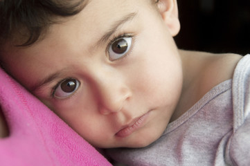Serious Hispanic boy resting head on chest of mother