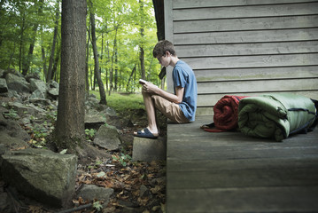 Caucasian boy reading book on wooden patio