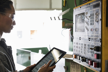 Mixed Race worker using digital tablet at control panel in factory
