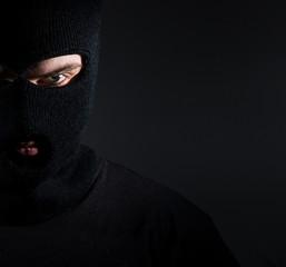 Man in a balaclava portrait, a thief on a dark background