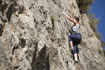 Female rock climber struggles to grip the edges on a challenging cliff.