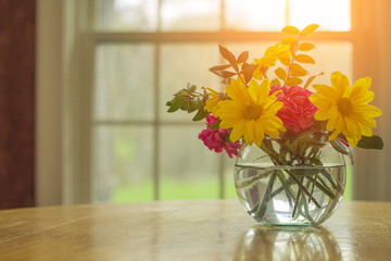 Sprint flowers assorted in vase with spring weather outside and open window fresh air concept with copy space.