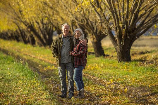 Caucasian couple hugging near trees in autumn