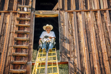 Portrait of smiling Caucasian farmer sitting on ladder in barn