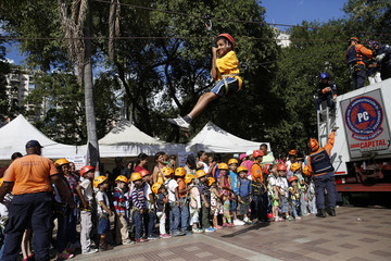 Child rides a zip-line during a rally against violence in Caracas