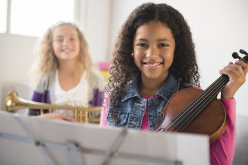 Smiling girls posing with violin and trumpet