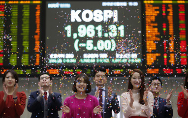 Employees of the Korea Exchange pose in front of the final stock price index during a photo opportunity for the media at the ceremonial closing event of the 2015 stock market in Seoul