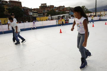 Children skate in an artificial ice rink set by the Town Hall at the slum district of Petare in Caracas