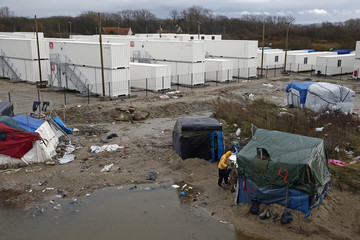 """A makeshift camp is seen in front of containers (rear) put into place to house several hundred migrants living in what is known as the """"Jungle"""" in Calais"""