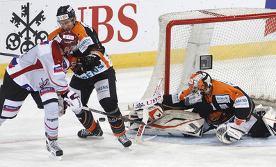 Dinamo Riga's Meija challenges Davis and goalkeeper Lang of Grizzly Adams Wolfsburg during their game at the Spengler Cup ice hockey tournament in Davos