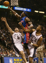 PISTONS CENTER WALLACE IS FOULED BY THE NETS KIDD AND COLLINS.