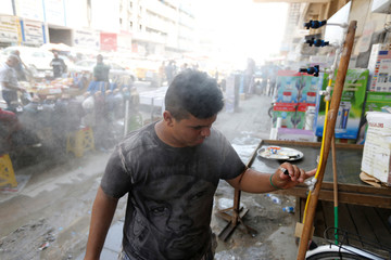 A man washes his face to cool off from the scorching summer heat in Baghdad