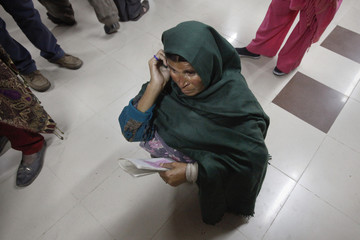 A woman kneels amid others waiting to receive free medication from a pharmacy at the Punjab Institute of Cardiology (PIC) in Lahore