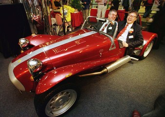 Roy Tso (R) from Winfield Motors and his guest James Gill laugh as they try the 40th anniversary roa..