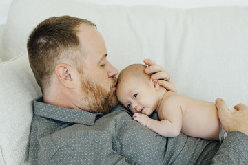 Father laying on sofa kissing baby daughter on head