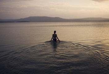 Silhouette of Caucasian woman wading in lake