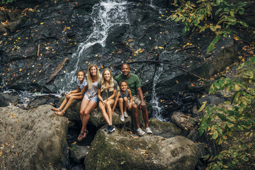Multi-ethnic family posing on rock near waterfall