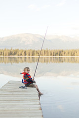 Caucasian boy sitting on dock at lake holding fishing rod